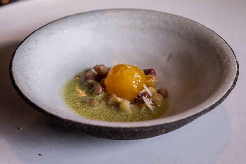 63-degree egg yolk served in rose oil sauce with vintage potatoes, Noma.