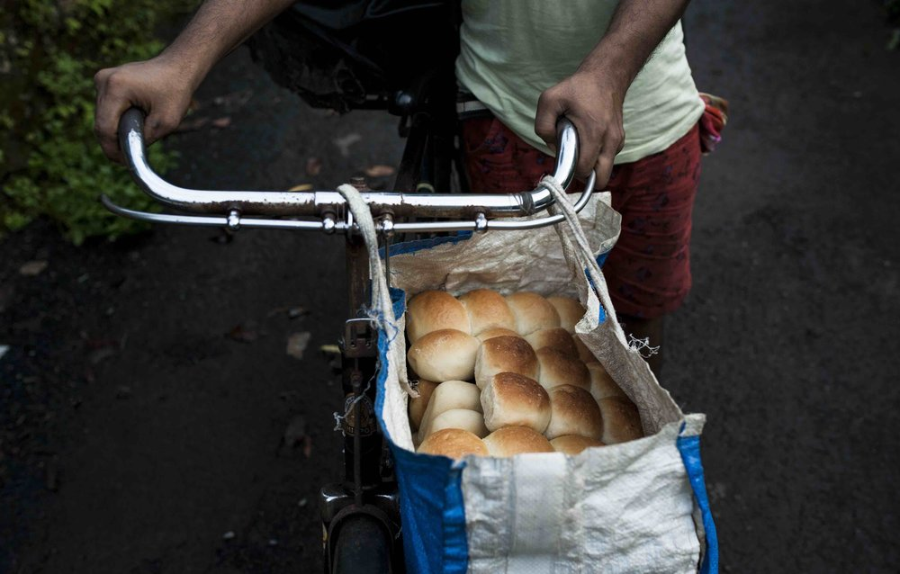 The poder (a word derived from Portuguese padeiro) starts the day before sunrise to bake the first batch of bread. He then heads out to deliver the bread on a cycle honking along, once at breakfast and again before dinner time.  Shot outside Gomez Bakery, Aquem Alto, Margao. 2017