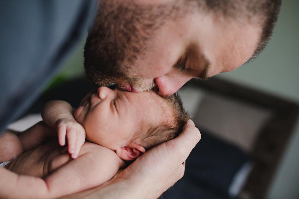 dad kissing newborn