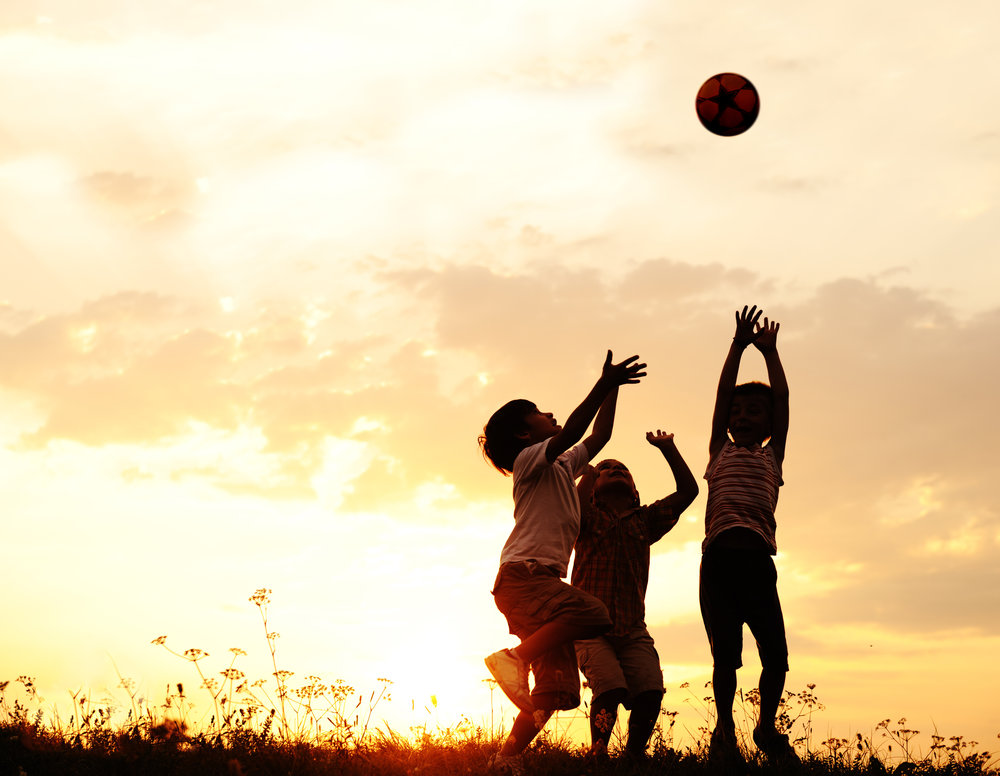 Three children playing ball in the light of the setting sun
