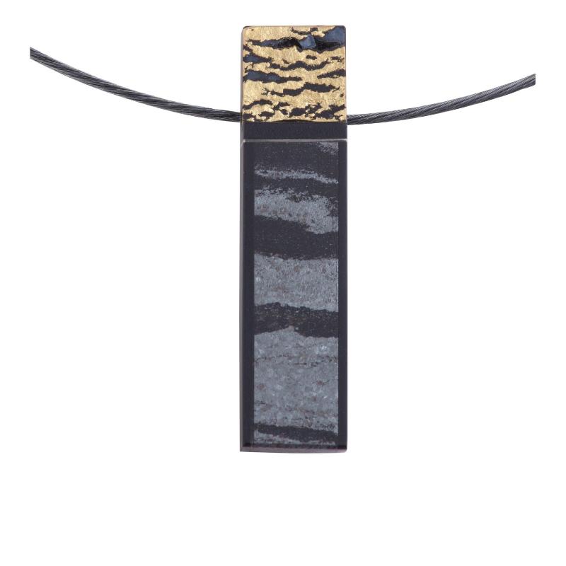 一枚赤铁矿石融合在长方形的墨玉上,是雕刻大师 SW 的作品。 这款独具匠心的新颖吊坠上面镶有 18K 金饰物,同时彰显明与暗的魅力。