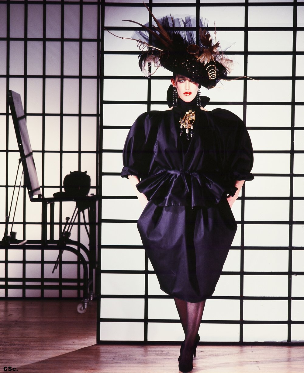 Sarah Hodgson - Kirby Wearing Black Interview Dress, Thames Garbage Hat - Jeweled Gallion from the Calanoli Collection, 1984, photograph by Joe Lyons