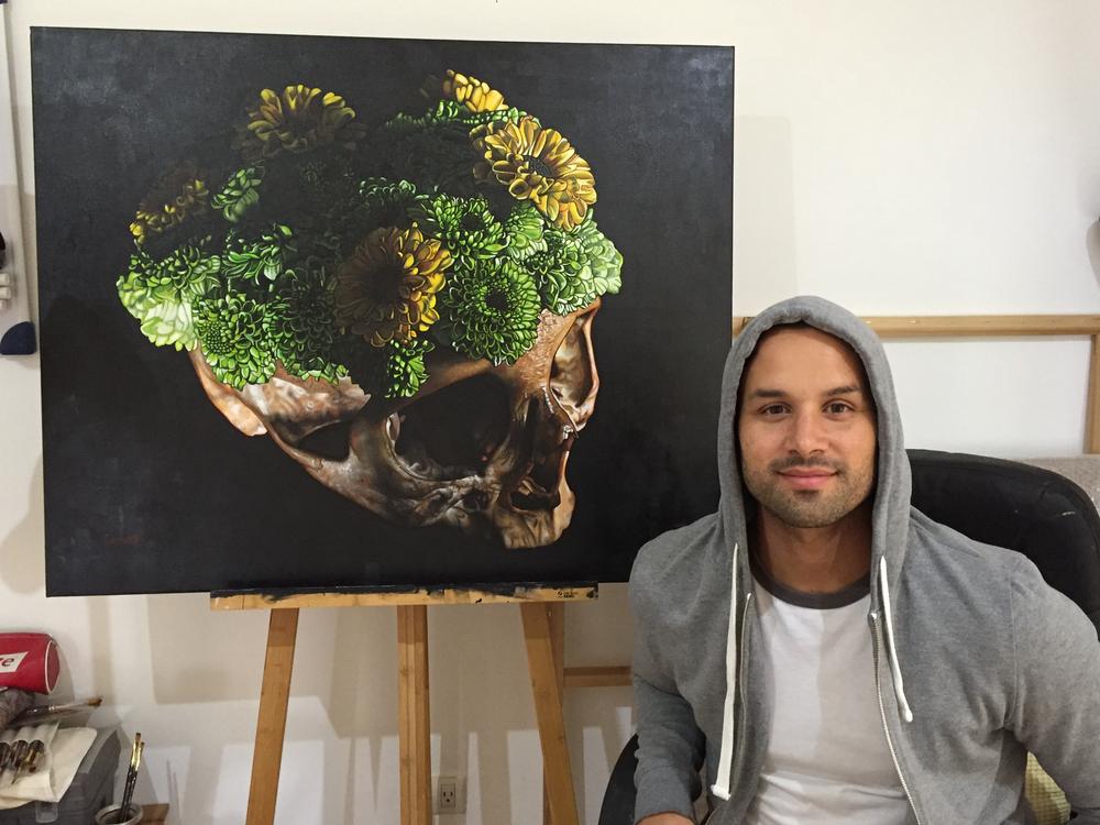 """Artist Chrispapita Escobar in his studio in Guatemala with his painting, """"Vanitas Nebula"""""""