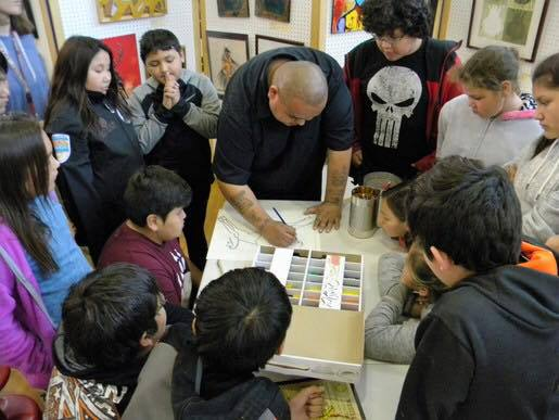 Pepion in his community teaching children the methods behind his art.
