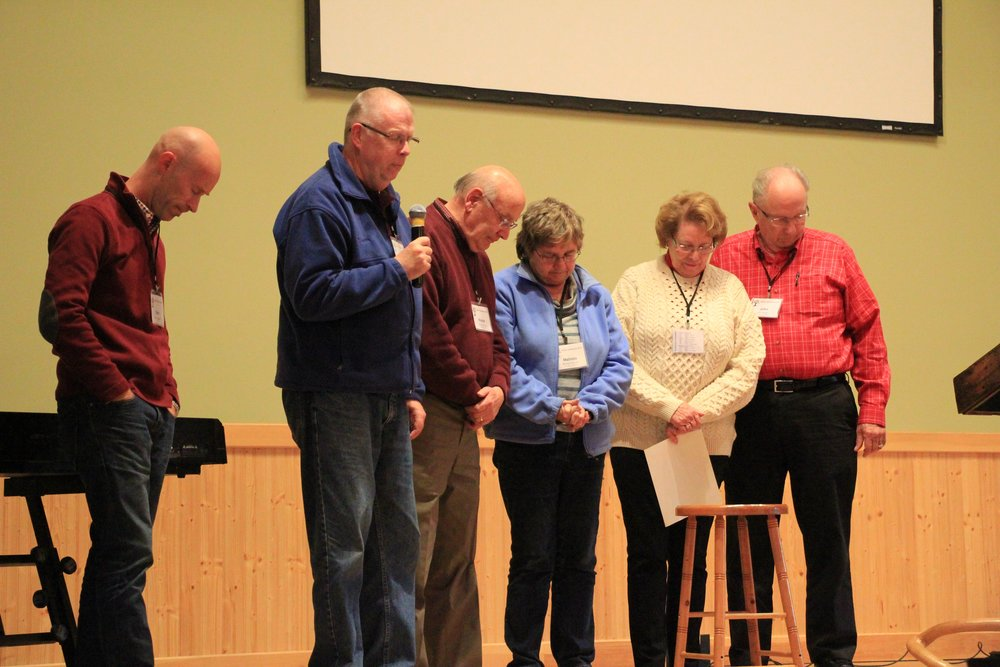 Praying for the Talcottville church. Left to right: Sam Huggard, John Westerholm, Wayne and Malinda Hansen, Sharon and John Backer.