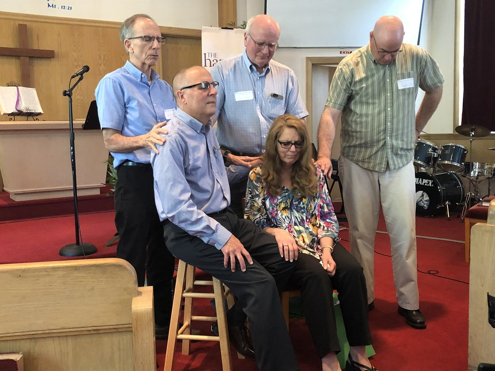 Ves Sheely (NEDA District Superintendent from 1999-2016), Jim McClymonds (Hope International Church Chairman), and Alex McDonough (Hope International Associate Pastor) pray for Paul and Nancy Reid.