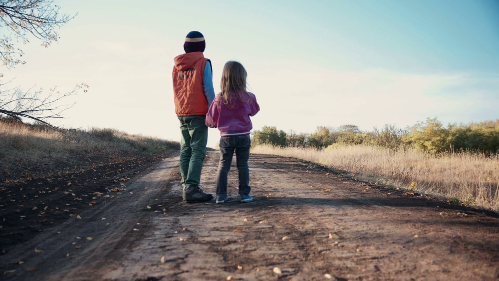 two-young-children-walking-away-from-the-camera-along-a-rural-dirt-road-in-evening-light-holding-hands-with-the-little-boy-taking-care-of-his-toddler-sister-then-he-start-to-play-football_bmvitvoc_thumbnail-full0.png