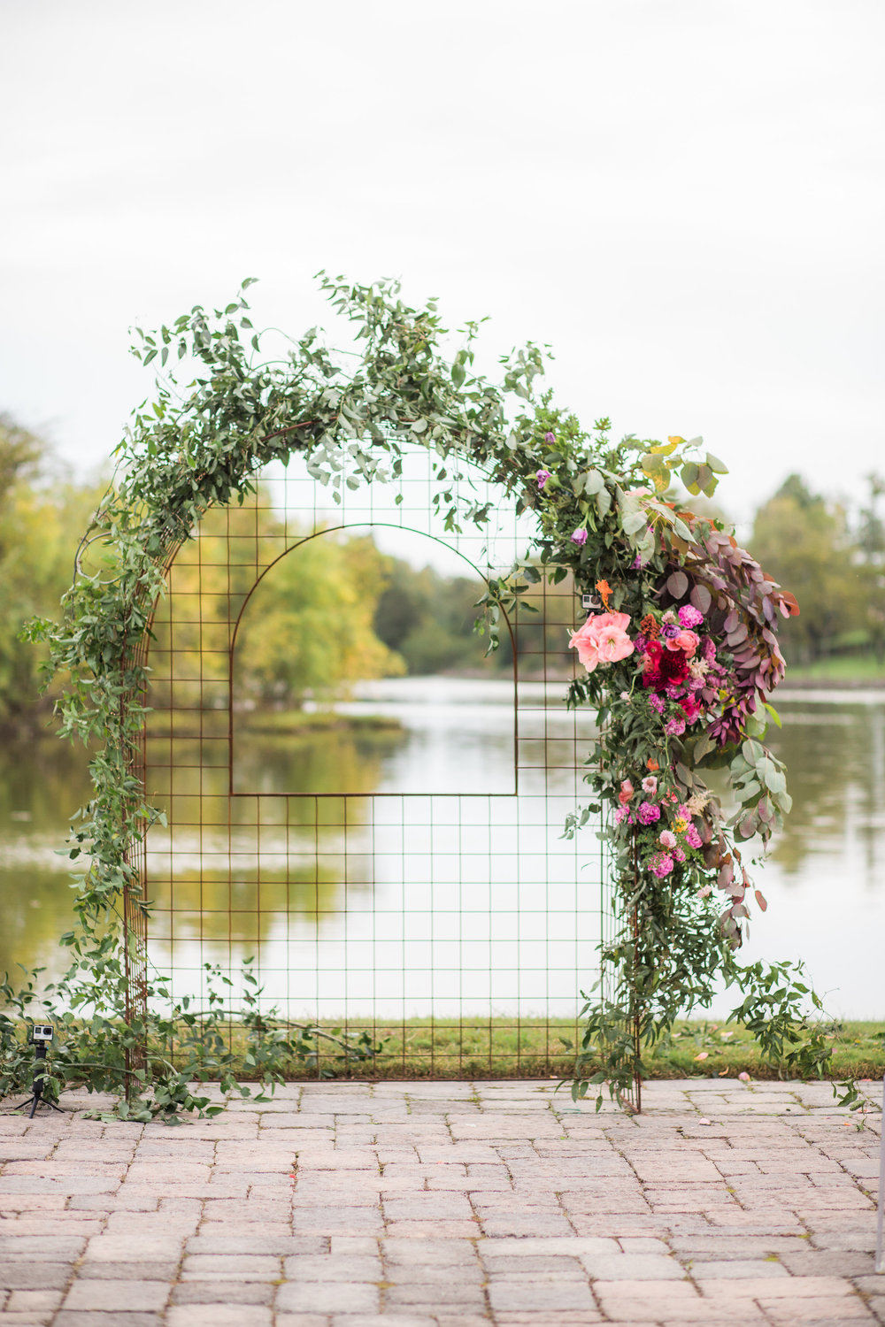 $1200 - installationLots of greenery with a cluster of many premium focal blooms, accessory blooms, and greenery trailing down the side of the arch.Finishes: Metal arch rental