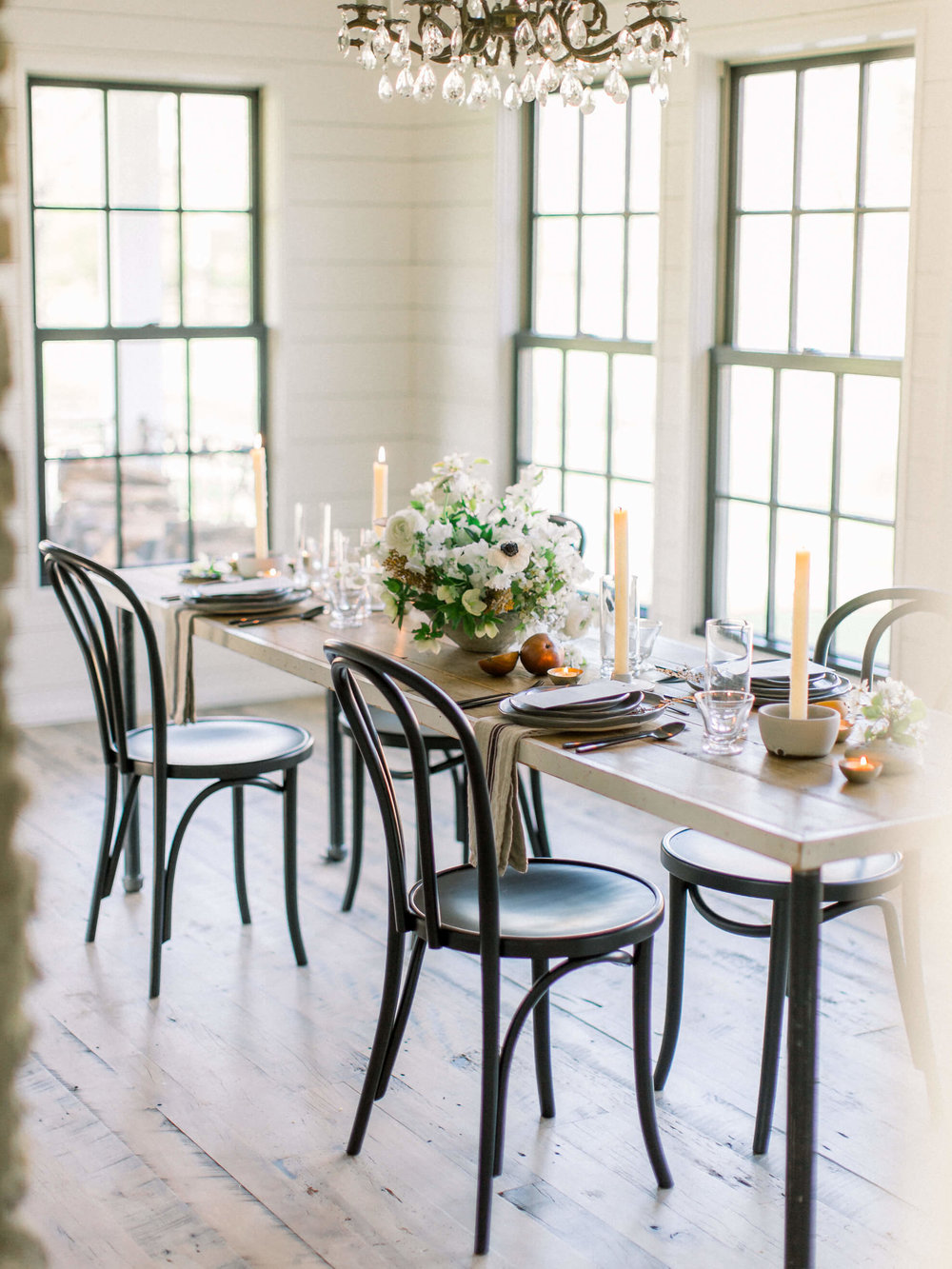 Winter Farmhouse Wedding - Our inspiration for this shoot came as the bareness of winter slowly transitions into the first blooms of spring. We wanted to create the feel of a small, elegant wedding, including the intimate moments as the couple prepared for their day, in this newly restored historic farmhouse just outside of Nashville, Tennessee. The home is filled with original details juxtaposed with modern farmhouse finishes that marry old and new. We designed with a harmonious color palette of soft whites paired with elegant grays, and deep blush tones with subtle hints of black. The details included a marriage of modern handmade ceramics, moody candlelight, the clean lines of black cafe chairs, florals created with heirloom roses and quince, and feminine blooms of light and airy sweet pea and anemone.