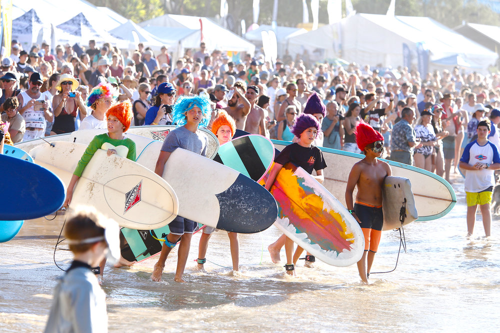 Massive crowd lines Noosa's Main Beach for the Costume Party Surf Exhibition.