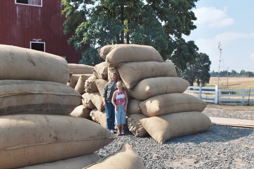 Long ago, Kathy and niece, Anna Martinsson, at Smitty Cox's farm, gathering wool bags from area farmers to be shipped in bulk to Utah.