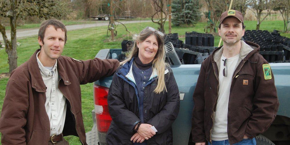 Chris Seal, U.S. Fish & Wildlife Service, Kathy Bridges and David Stroppel, Oregon Department of Fish & Wildlife, meet in March to discuss project options. In the truck behind them are empty containers which previously contained plugs of various wetland plants.