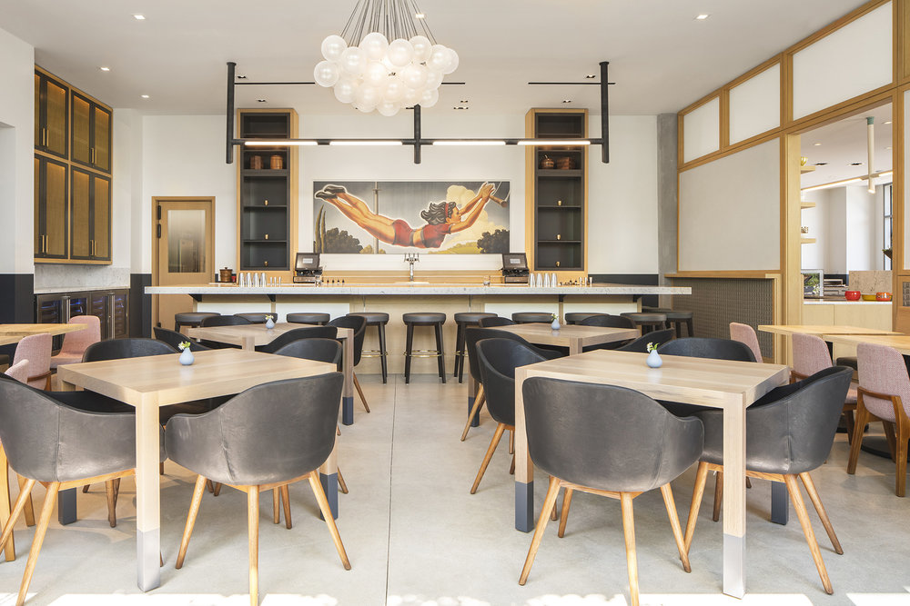 In the main dining room at Spoonfed, custom LED track lighting was designed to have a presence over the bar.