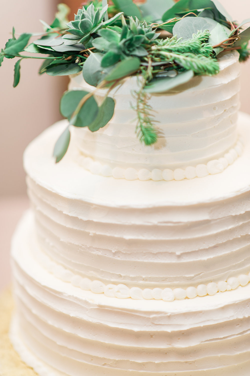 gorgeous natural white wedding cake with greenery