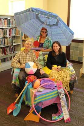 Friends Treasurer Teresa, holding the umbrella, gets in the mood for Beach Books & Bling summer book sale with Friends.
