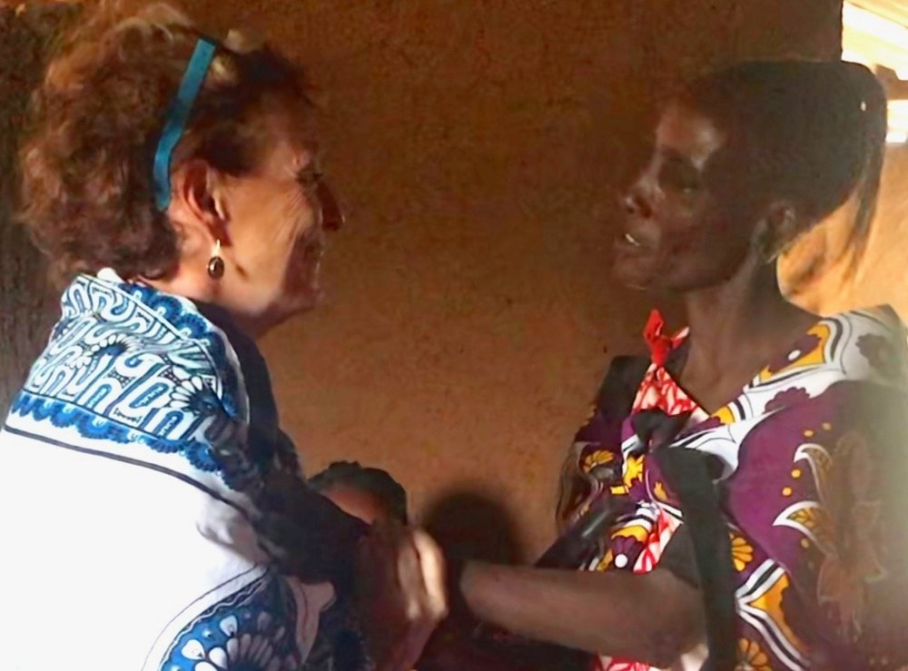 The mother of Mercy and Agnes presenting Kim with traditional Maasai gifts