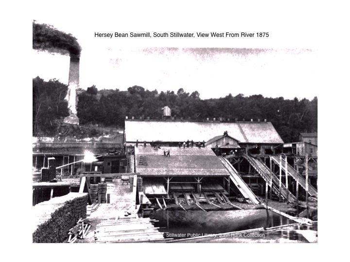 The Hersey Bean Lumber operation was located in South Stillwater across from Slab Alley, near the site of the Aiple Home and the present Oasis Cafe.  The river access was important to receiving lumber from the north via the Boomsite as well as for rafting operations to ship cut lumber via the St. Croix and Mississippi rivers before the railroads in 1872. Remnants of this operation can still be found along the walking path between the Lift Bridge and the New Bridge.  The base of the chimney still stands at the location on the Stillwater bluff above the river.