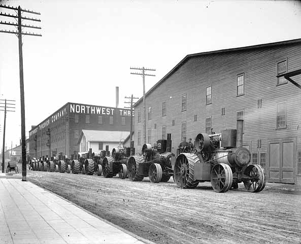 """This is a promotional photo of one """"Minnesota Giant"""" pulling ten other steam traction engines along north Main Street, Stillwater, MN in 1909."""