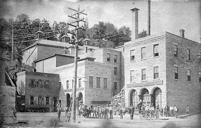 "The view is to the southwest from the corner of Main and Nelson Streets.  The date is after 1866, but before 1873. These buildings still stand today and became part of the Wolf Brewing Complex. To view this same location as a ""Time Tunnel"" from 1873 to 2016, click or tap the above photo. Photo Credit, New York City Public Library, John Sinclair."