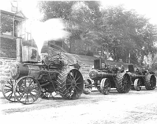 Main Street, south of the Territorial Prison. The view is to the northwest. The subject matter is are the fire-breathing traction engines manufactured by The Northwest Thresher Company. Photo credit is The Stillwater Public Library, John Runk Collection. Click or Tap the photo above to view this same location today.