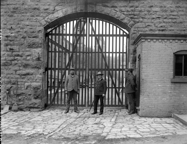 "Stillwater Territorial Prison Main Gate, located on Main Street.  The year is 1907.  The photo shows a guard and two prisoner trustees.  Photo Credit is The Stillwater Public Library, John Runk Collection. Click or Tap on this photo to reveal a ""Time Tunnel"" photo of this same location from 1910 to 2016."
