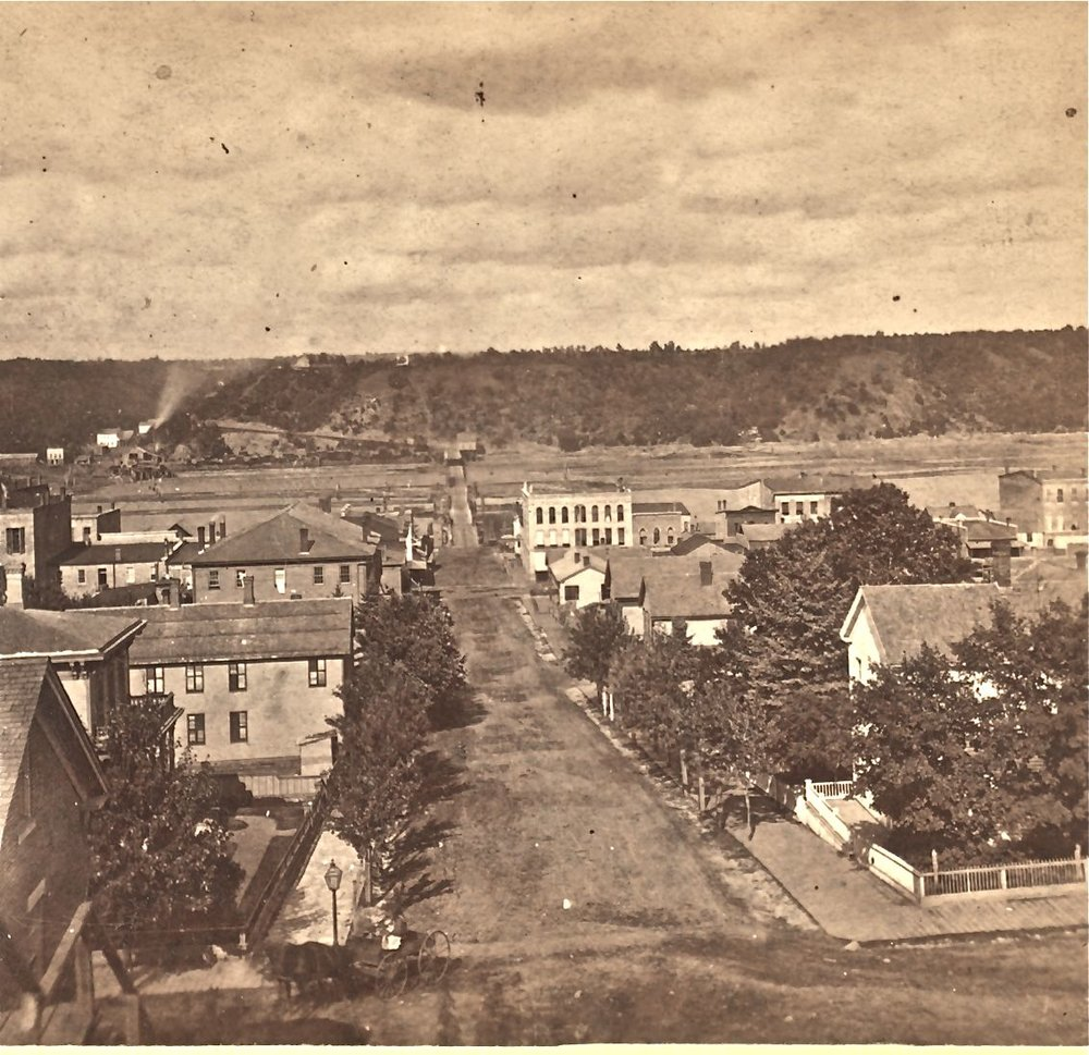 "This is a view from the Chestnut Street Stairway, near Third Street, looking east toward the pontoon bridge. The photo is from a stereo photo taken by John Sinclair ca. 1875.  The photo is sourced from the New York City Public Library.  This was before the trolleys appeared.  Lumber mills are visible on the Wisconsin side of the St. Croix River.  To see a ""Time Tunnel"" photo between this period and 2016, click or tap the above photo."