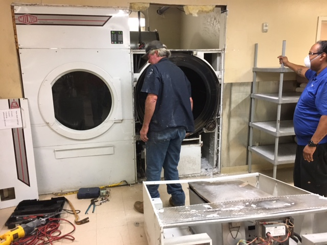 Old 120 lb. dryer on right coming out.  This dryer comes in two pieces and the top control unit has already been removed and is on the floor in the bottom right of the pic.