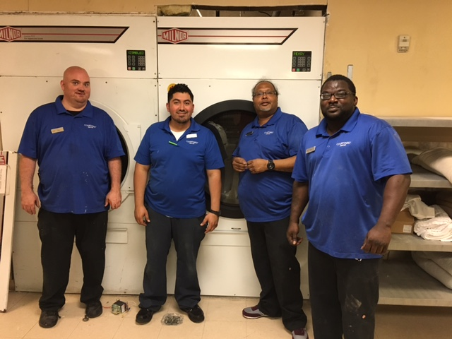Here is Andre (second from right) and his engineering crew standing in front of their new Milnor 120 lb. dryer.