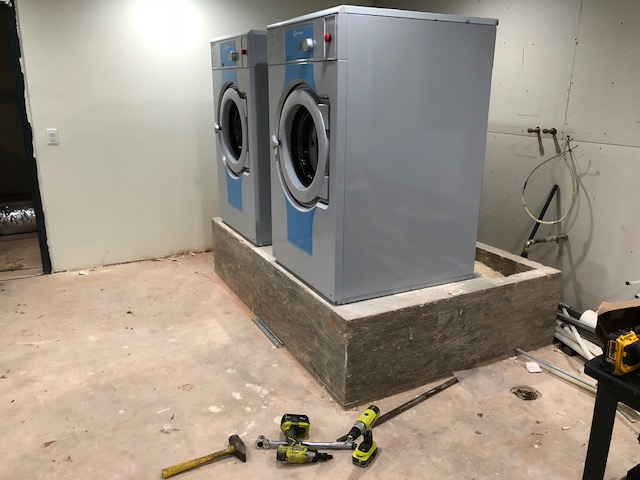 "This concrete pedestal was poured 24"" high.  6"" would be sufficient.  The laundry workers will have to stretch to operate the controls.  It wasn't much fun getting the machines up there."