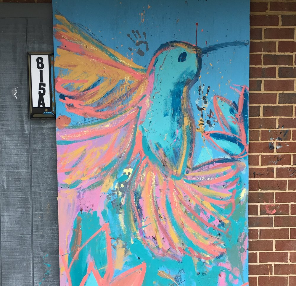 "In addition to the large ""Slam Dunk"" mural near the basketball court, participants added colorful murals to some of the boarded-up windows and doors in the community"