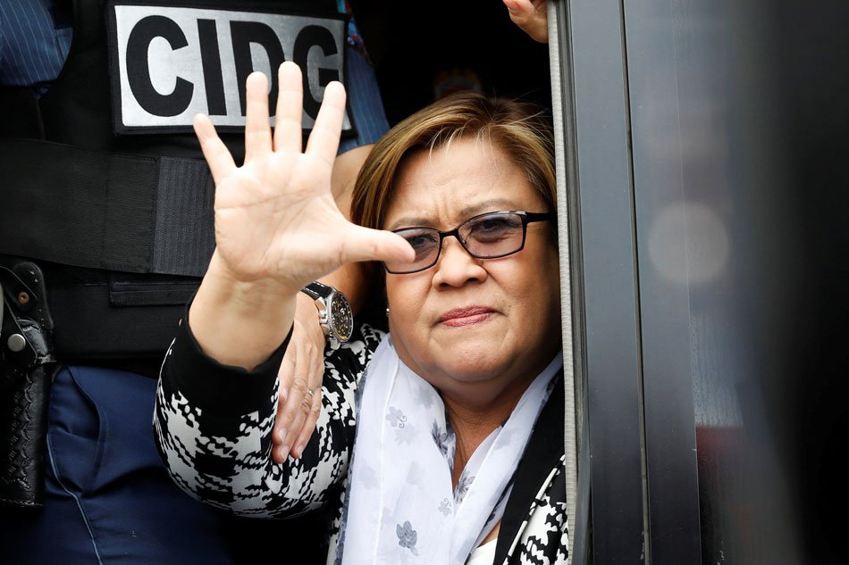 Senator de Lima flashes her signature sign, symbolizing a call to stop injustices