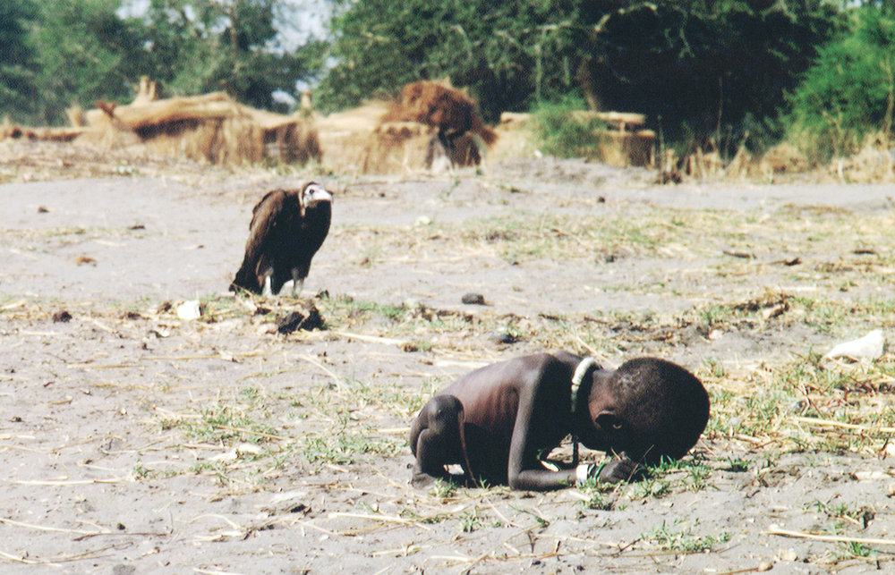 Starving Child and Vulture    Kevin Carter   1993   'As he took the child's picture, a plump vulture landed nearby. Carter had reportedly been advised not to touch the victims because of disease, so instead of helping, he spent 20 minutes waiting in the hope that the stalking bird would open its wings. It did not. Carter scared the creature away and watched as the child continued toward the center. He then lit a cigarette, talked to God and wept. The New York Times ran the photo, and readers were eager to find out what happened to the child—and to criticize Carter for not coming to his subject's aid. His image quickly became a wrenching case study in the debate over when photographers should intervene.' ( http://100photos.time.com/photos/kevin-carter-starving-child-vulture )