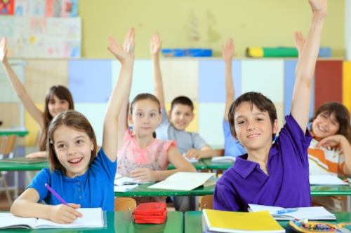 Elementary-school-students-raising-hands-in-classroom..jpg