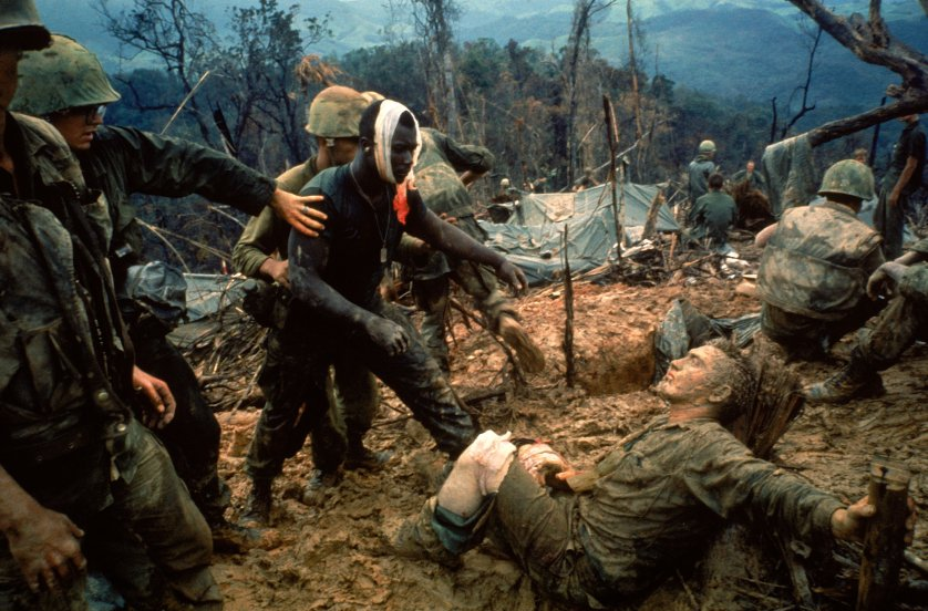 Wounded Marine Gunnery Sgt. Jeremiah Purdie (center, with bandaged head) reaches toward a stricken comrade after a fierce firefight south of the DMZ in Vietnam in Oct. 1966..jpg