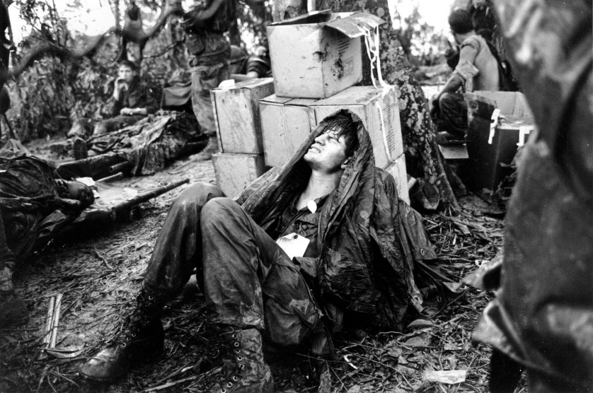 A wounded U.S. paratrooper grimaces in pain as he awaits medical evacuation at base camp in the A Shau Valley near the Laos border in South Vietnam on May 19, 1969..jpg