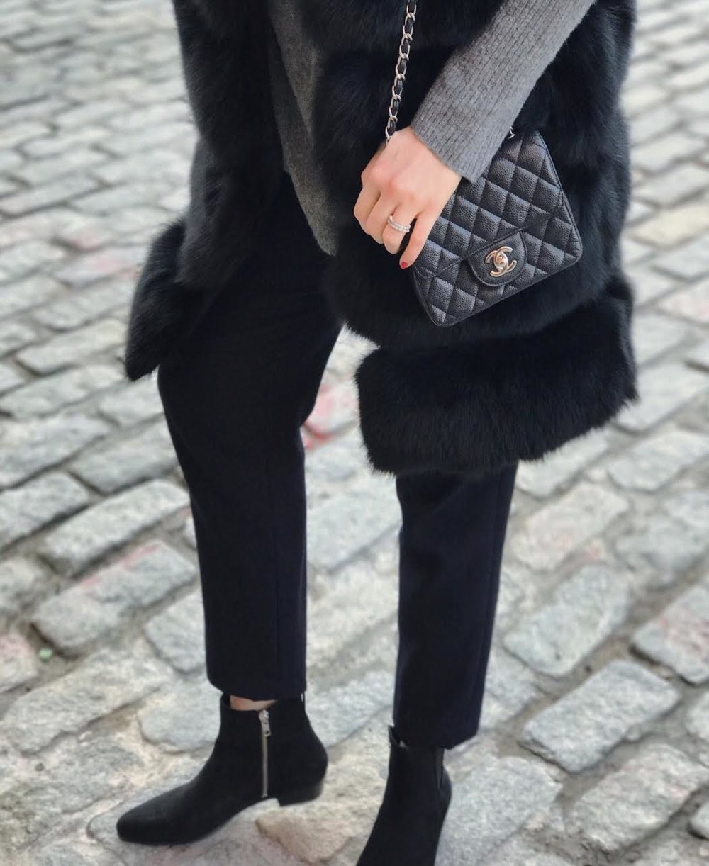 black fur waistcoat, grey cashmere sweater, Comme des Garçons navy wool trousers, Isabel Marant suede ankle boots, mini Chanel bag.