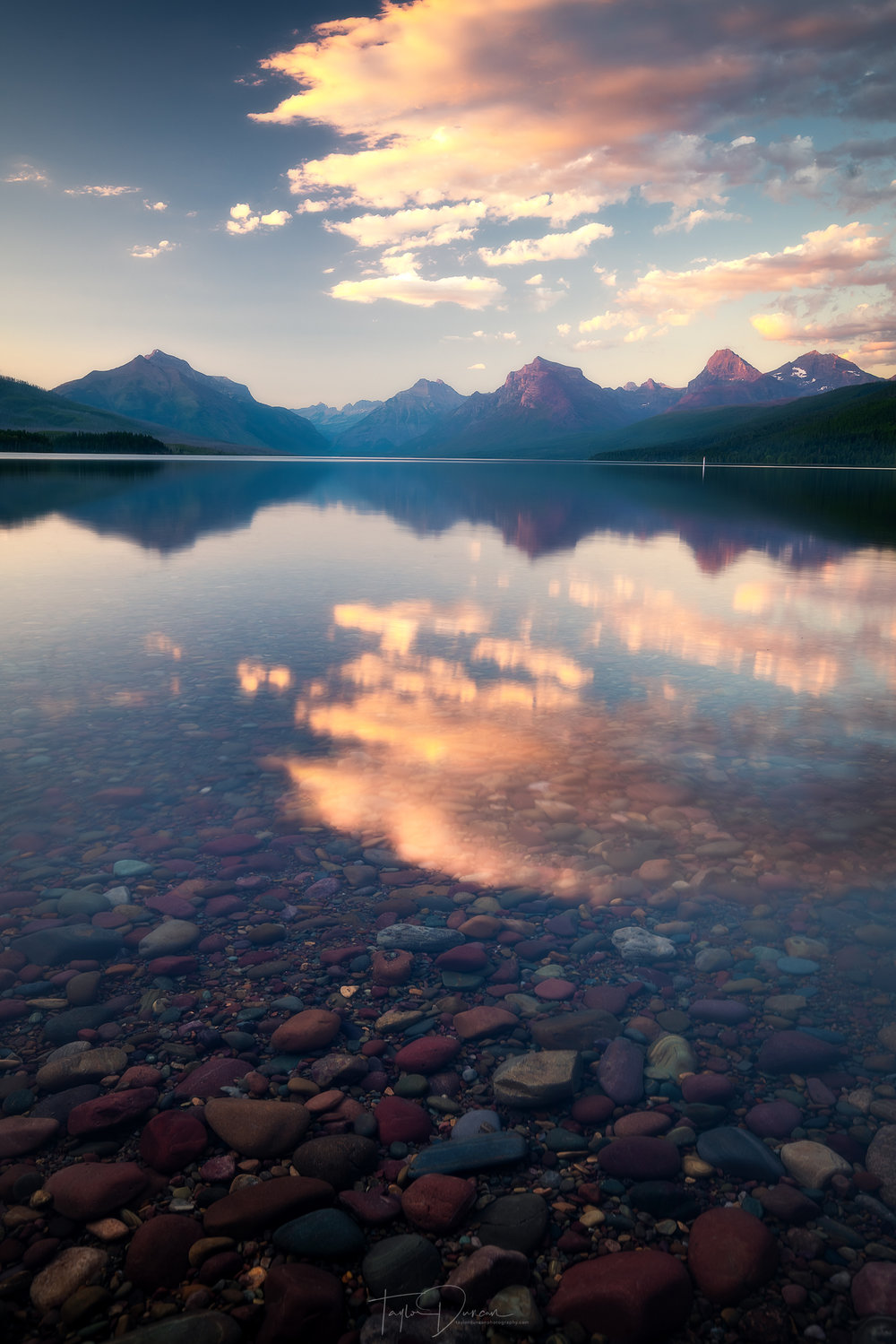 A colorful sunrise lights up the distant peaks over Lake McDonald