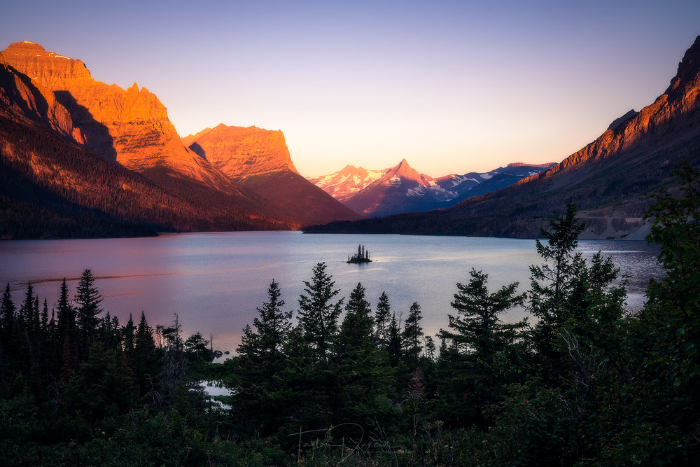 Sunrise illuminates the peaks surrounding St. Mary Lake and Wild Goose Island showing one of the most iconic views in the park
