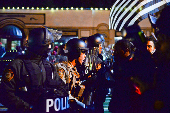 St. Louis County Police officers yell for protestors to step back after riots broke out on West Florissant Avenue in Ferguson, Mo. (Photo by Nathan Hoefert, courtesy of Daily Egyptian)
