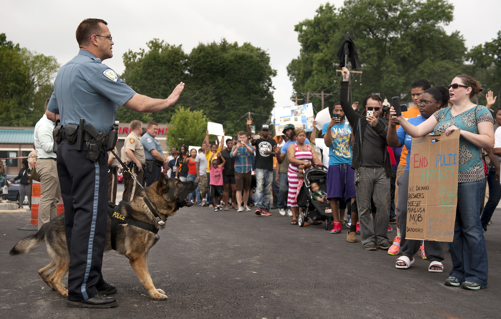 Protestors confront police during an impromptu rally, Sunday, Aug. 10, 2014 to protest the shooting of 18-year-old Michael Brown, in Ferguson, Mo., Saturday, Aug. 9, 2014. Police said Brown, who was unarmed, was fatally shot Saturday in a scuffle with an officer. (AP Photo/Sid Hastings)