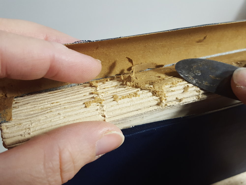 Removing brittle animal glue and spine lining.