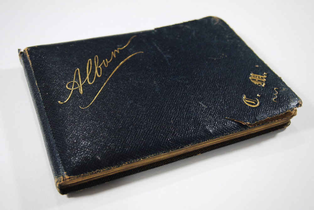 The 19th century album has been personalized with the owner's initials in the bottom right corner.