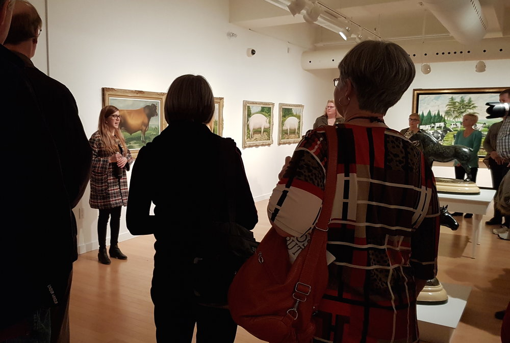 Curatorial and Collections Assistant Samantha Purvis-Johnston address visitors at the opening reception of  Ross Butler: Branding, Butter and Bulls , at the Woodstock Art Gallery.
