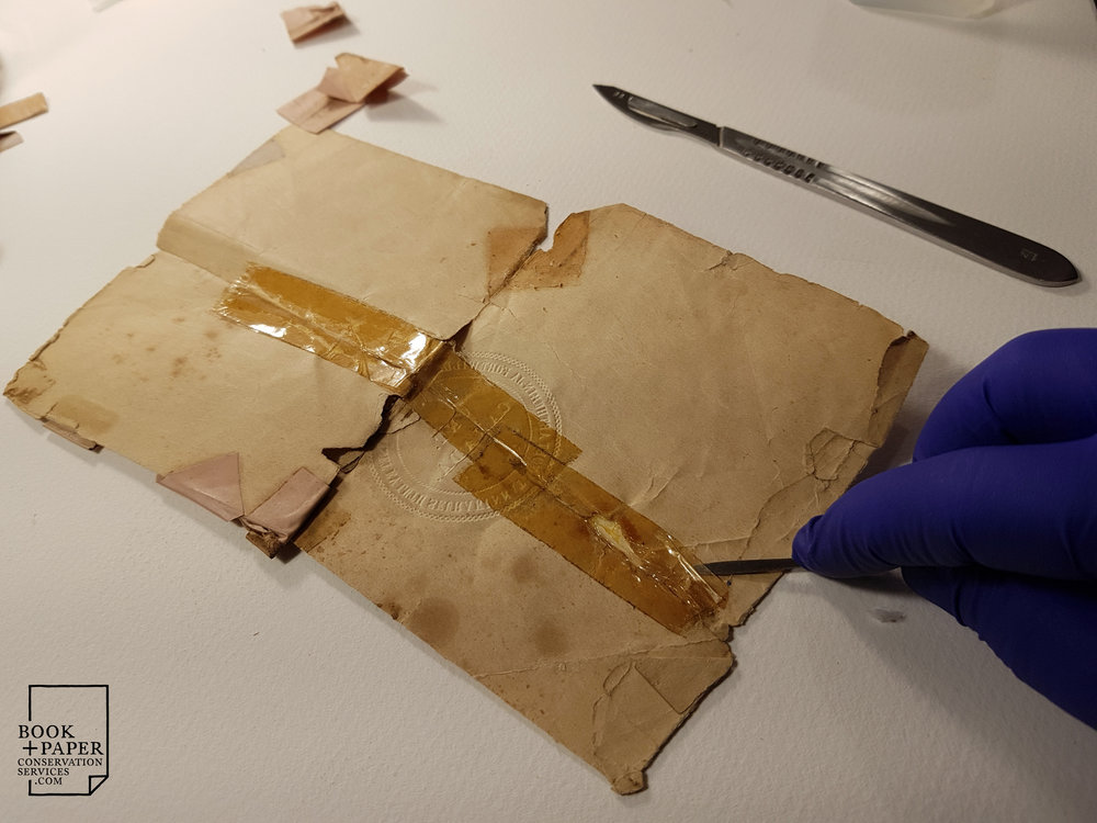 Removing various tapes from the document with scalpel and solvent.