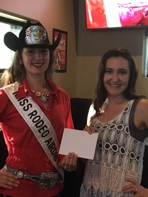 Miss Rodeo Airdrie Sarah Pack presents Janine Hartsook of PUSH Cycle with Airdrie Pro Rodeo's contribution.