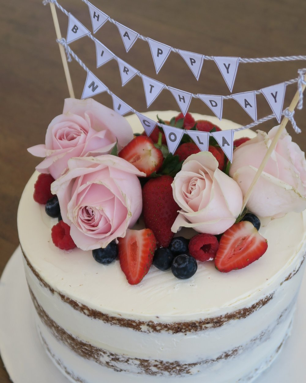 Semi naked chocolate cake with fresh flowers and bunting.jpg