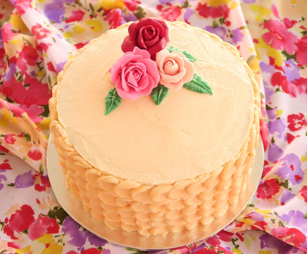 Pink buttercream scallop design with fondant flowers.jpg