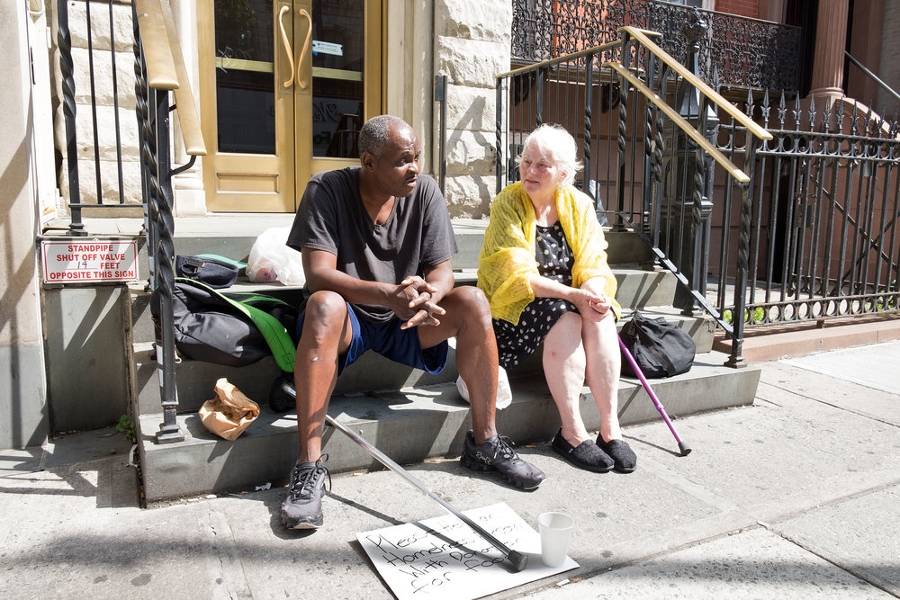 Talking with Nate, a  man who panhandles next to her shelter. East Village, NY (August 13, 2017).