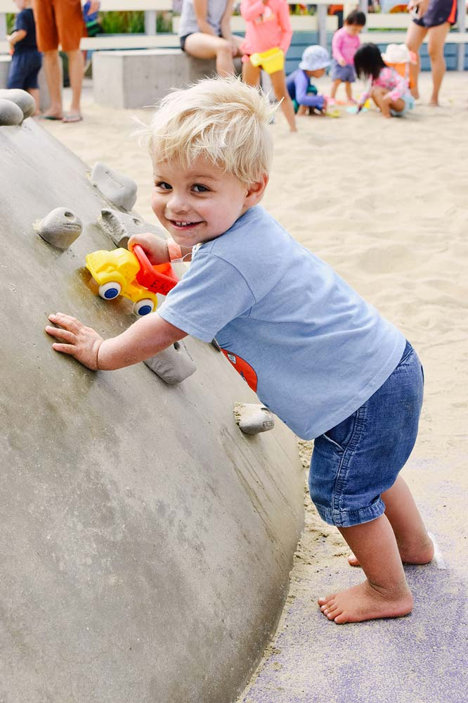 Aiden learned how to climb this rock at  Annenberg Beach  during the party which made him so happy!