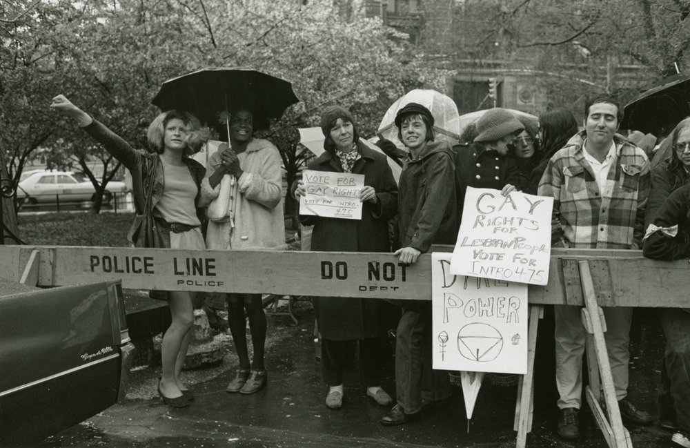 Marsha P. Johnson holds an umbrella as she and Sylvia Rivera march for Pride.